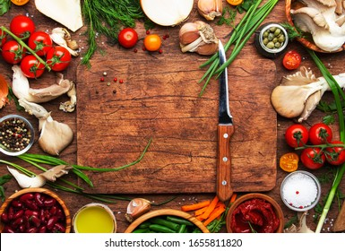 Food cooking background, ingredients for preparation vegan dishes, vegetables, roots, spices, mushrooms and herbs. Cutting board, chef knife. Healthy food concept. Rustic wooden table, top view
