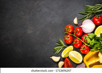Food cooking background on black stone table. Fresh vegetables, spices, herbs and oil. Ingredients for cooking with space for your text.
