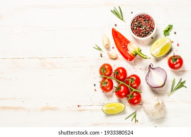 Food cooking background on white wooden table. Fresh vegetables, spices, herbs and oil. Ingredients for cooking. Top view with copy space.