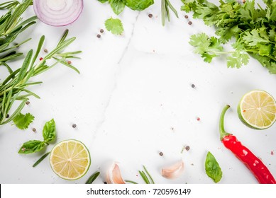 Food cooking background, white marble table. Spices, herbs for dinner - coriander, parsley, basil, rosemary, lime, tomato, salt, pepper, garlic, onion, red chili pepper. Copy space top view, frame