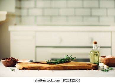Food cooking ingredients on white kitchen design interior background with rustic wooden chopping board in center, copy space.