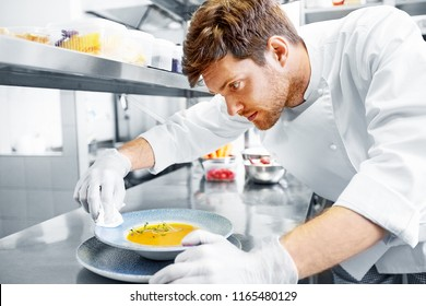 food cooking, profession and people concept - happy male chef cook serving and cleaning plate of soup at restaurant kitchen