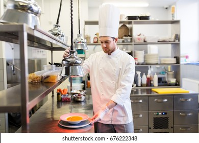 food cooking, profession and people concept - happy male chef cook with cloche serving plate of soup at restaurant kitchen