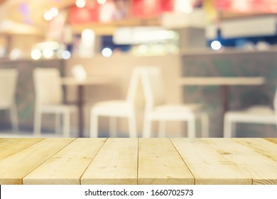Food court or food center in shopping mall. Interior consist of table, chair, restaurant, coffee shop. Similar of canteen for shopping mall. Wood table top for product display or blurred background.