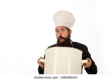 Food, cuisine, cookery and gastronomy. Kitchen utensils and professional cookery concept. Bearded man in chef uniform with saucepan. Male chef with big pot. Chef in cap and apron holds big saucepan.