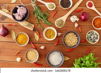 food, culinary and eating concept - bowls with different spices, onion, garlic with pine nuts and red hot chili pepper on wooden table