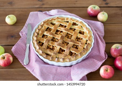 food, culinary and eating concept - close up of apple pie in baking mold with knife on kitchen towel