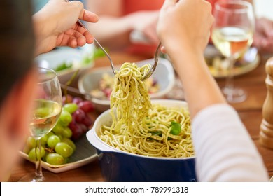 food, culinary and eating concept - hands taking pasta with basil from bowl on table