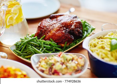 food, culinary and eating concept - roast chicken with garnish of green beans on served table