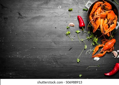 The food delicacies. Boiled crawfish with herbs and spicy peppers. On a black chalkboard.