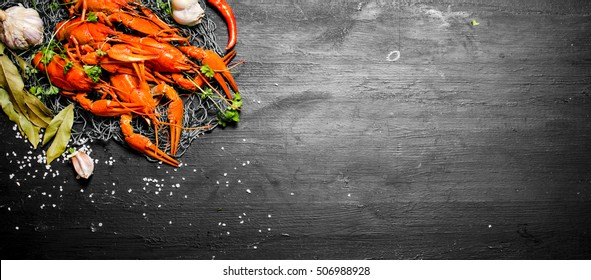 The food delicacies. Fresh boiled crawfish with spices and herbs. On a black chalkboard.