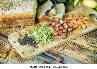 Food. Delicious nuts, seeds, spices.  Almond, hazelnut, sunflower seeds, pepper, salt. Greenery. Fresh vegetables.