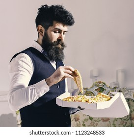 Food delivery concept. Macho in classic clothes hungry, holds slice of cheese pizza, eats, enjoying taste, interior background. Man with beard and mustache holds box with tasty fresh hot pizza.