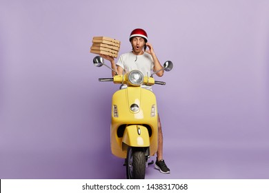 Food delivery concept. Shocked courier takes order over phone from customer, holds stack of cardboad pizza boxes, stops to have break drives fast motorbike, astonished to loose way, doesnt know route