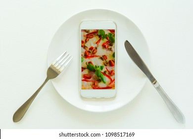 Food delivery concept. Top view on smartphone with pizza on screen laying on plate on white wooden table