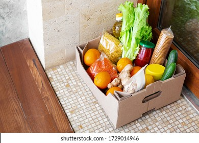 Food delivery or Donation Box during covid quarantine. Contactless social home delivery, safe shopping in coronavirus pandemic. Takeout meal. Food box on doorstep near door. Courier home delivery