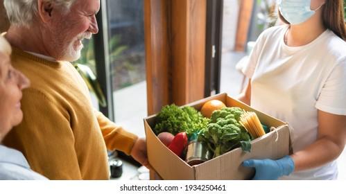 Konzept der Abgabe oder Spende von Nahrungsmitteln. Junge Frau in Handschuhen und Schutzmaske liefert eine Schachtel von Essen ältere Ehepaare zu Hause