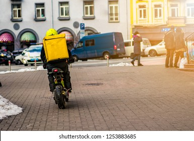 Food delivery driver with yellow backpack on a motorcycle riding along a street