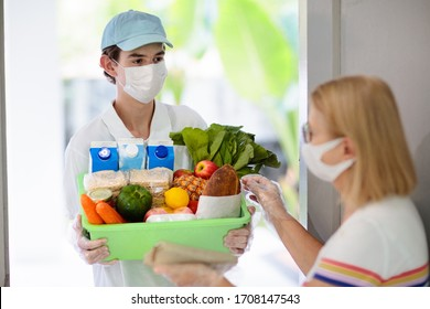 Nahrungszufuhr während des Ausbruchs des Corona-Virus. Kurierer tragen Gesichtsmaske, die Lebensmittel Ordnung in der Coronavirus-Epidemie. Sicherer Einkauf in einer Pandemie. Essen mitnehmen. Menschen lagern Nahrungsmittel.