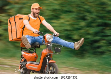 A food delivery man in an orange uniform on a moped with a food delivery bag flies at high speed with his legs apart.