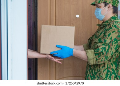 food delivery to the military to your home. assistance to pensioners, the poor and the population. a courier, a soldier in rubber gloves passes by the box. main products at the door