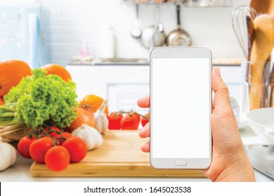 Food delivery / online ordering service. Concept / Woman holding a blank phone screen on the kitchen background and your editing area.