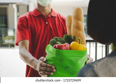food delivery service man with protection face mask in red uniform holding fresh food set bag to customer at door home, express delivery, quarantine, virus outbreak, takeaway food delivery concept