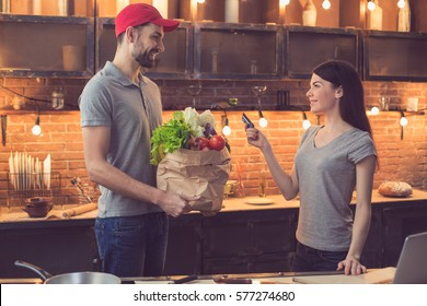 Food delivery service. Young man bringing fresh food. Young woman paying with credit card. Nice loft kitchen interior with light bulbs