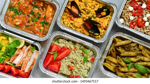 Food delivery.Different aluminium lunch box with healthy natural food pasta pesto, spelt, paella, quinoa, chicken salad, curry.  airlines food. airline meals and snacks . takeaway