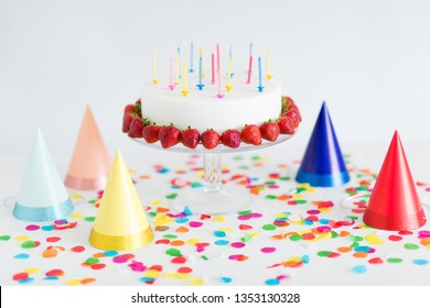 food, dessert and party concept - birthday cake with candles and strawberries on stand