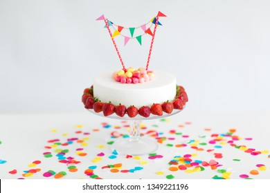 food, dessert and party concept - close up of birthday cake with candies, garland and strawberries on stand