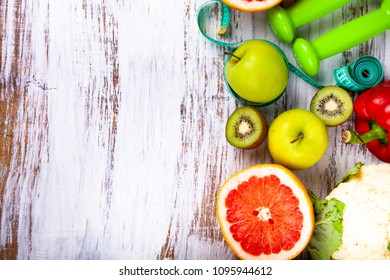 Food for  diet and dumbbells on a wooden background. Concept of diet and healthy lifestyle.