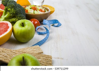 Food for diet and measuring tape on a wooden table. Concept of diet and healthy lifestyle.