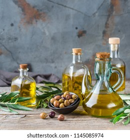 Food diet and nutrition concept. Assortment of fresh organic extra virgin olive oil in bottles with green leaves on a rustic wooden table