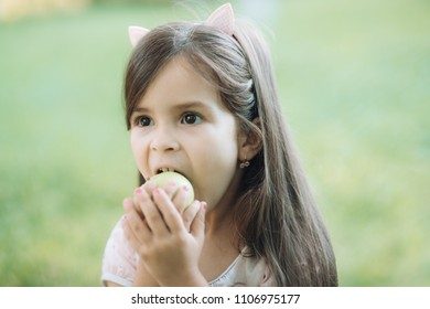 Food, diet, vitamin. Child with green apple fruit on nature, food. Freshness youth growth nutrition. Health healthcare, healthy dieting. Little girl eat apple on natural background, vitamin
