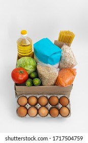 Food donations box on gray background. Cabbage, cucumber, tomatoes, flour, sunflower oil, spaghetti, oatmeal, lentils, eggs in box.