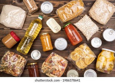 Dons alimentaires tels que pâtes, riz, huile, beurre d'arachide, conserves, confitures sur table en bois marron, vue de dessus