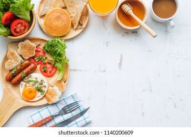Food and drink concept, breakfast set with eggs, sausages, toasts and fresh vegetable on rustic white wooden table