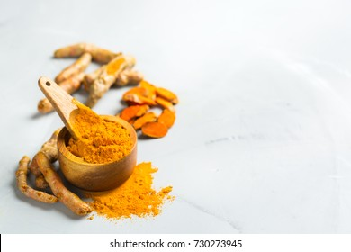 Food and drink, diet nutrition, health care concept. Organic orange turmeric root and powder, curcuma longa on a cooking table. Indian oriental low cholesterol spices. Copy space background