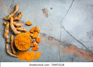 Food and drink, diet nutrition, health care concept. Raw organic orange turmeric root and powder, curcuma longa on a grunge cooking table. Indian oriental low cholesterol spices. Copy space background