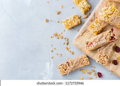 Food and drink, dieting, nutrition breakfast concept. Healthy homemade cereal granola muesli bars with oats, nuts, dry berries on a cozy kitchen table. Top view flat lay copy space background