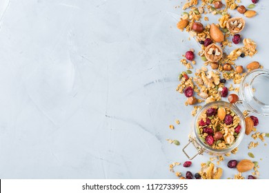 Food and drink, dieting, nutrition breakfast concept. Healthy homemade cereal granola muesli with oats, nuts, dry berries on a cozy kitchen table. Top view flat lay copy space background