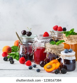 Food and drink, harvest summer autumn concept. Assortment of seasonal berries and fruits jams in jars on a wooden table. Rustic background