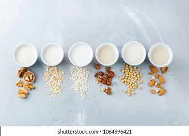 Food and drink, health care, diet and nutrition concept. Assortment of organic vegan non diary milk from nuts, oatmeal, rice, soy in glasses on a kitchen table. Copy space top view flat lay background