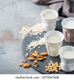 Food and drink, health care, diet and nutrition concept. Assortment of organic vegan non diary milk from nuts, oatmeal, rice, soy in glasses on a kitchen table