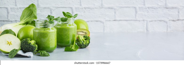 Food and drink, healthy dieting and nutrition, lifestyle, vegan, alkaline, vegetarian concept. Green smoothie with organic ingredients, vegetables on a modern kitchen table. Copy space banner