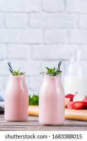 Food and drink, healthy dieting and nutrition, lifestyle, vegan, alkaline, vegetarian concept. Pink smoothie with banana and strawberry on a modern kitchen table. Copy space background