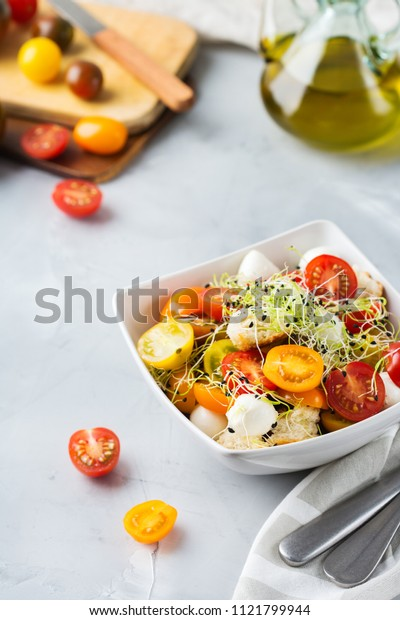 Food and drink, healthy eating concept. Salad with assortment of organic cherry tomatoes, mozzarella cheese, toasted bread and microgreen on a kitchen table