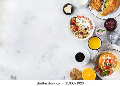 Food and drink, healthy morning eating concept. Breakfast assortment with pancakes, waffles, croissant sandwich and granola with yogurt on the kitchen table. Top view flat lay copy space background