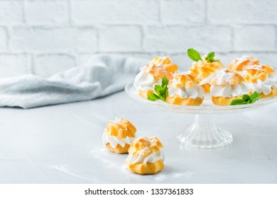 Food and drink, holidays concept. Delicious sweet homemade profiteroles with cream on a modern kitchen table. Copy space background